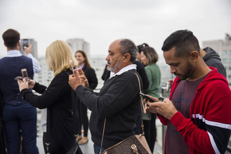 Pessoas utilizam telefone celular no mirante do Sesc Paulista