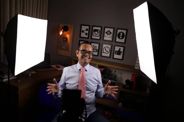 Homem com óculos, camisa social, gravata e sorrindo, sentado em um banco, em cada um de seus lados refletores para filmagem. Ao fundo mesa de escritório, parede cinza e alguns quadros de fundo branco com símbolos como o botão de curtir, logo do instagram, entre outros.