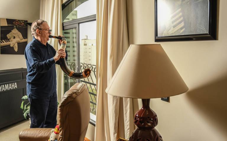 O músico Caçulinha toca o berrante que ganhou do cantor Sérgio Reis na janela de seu apartamento, no Jardim Paulistano, zona oeste de São Paulo