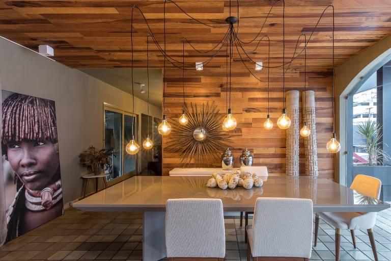 Sala de jantar com parede e teto de madeira, mesa de madeira quadrada, cadeiras brancas e quadro de indígena apoiado no chão