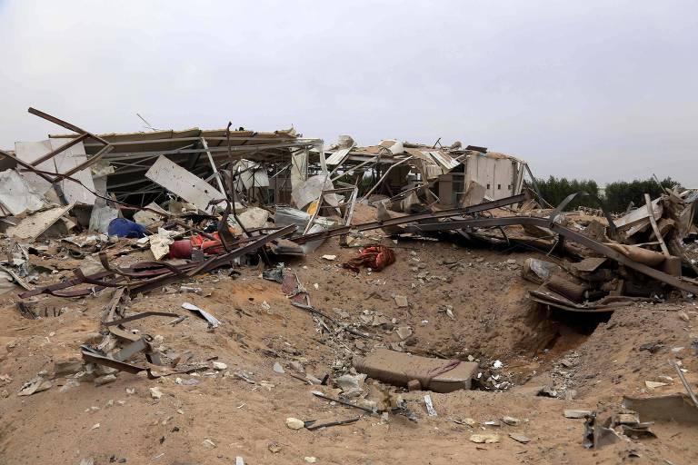 Destroços e cratera deixados por bombardeio americano contra alvos pró-Irã no Iraque em retaliação por ataque que matou dois militares americanos e um soldado britânico
