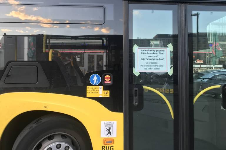 Ônibus que circulam em Berlim trazem cartaz com aviso de que porta dianteira do veículo está trancada para evitar contato entre motorista e passageiros