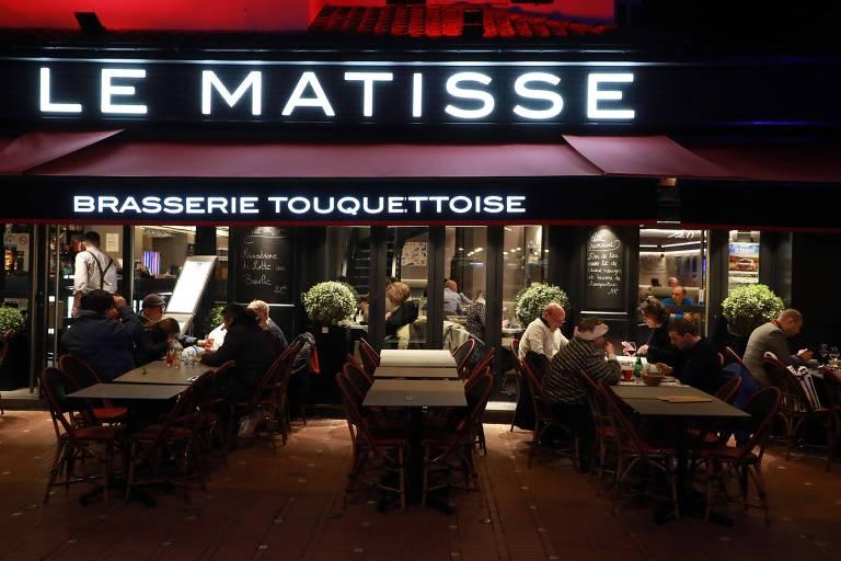 Pessoas sentadas e mesa na calçada, em frente ao um café, à noite