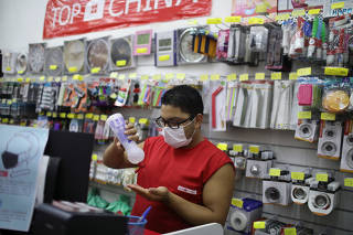 A shopkeeper cleans his hands and wear a protective mask, amid coronavirus fears, in Rio de Janeiro