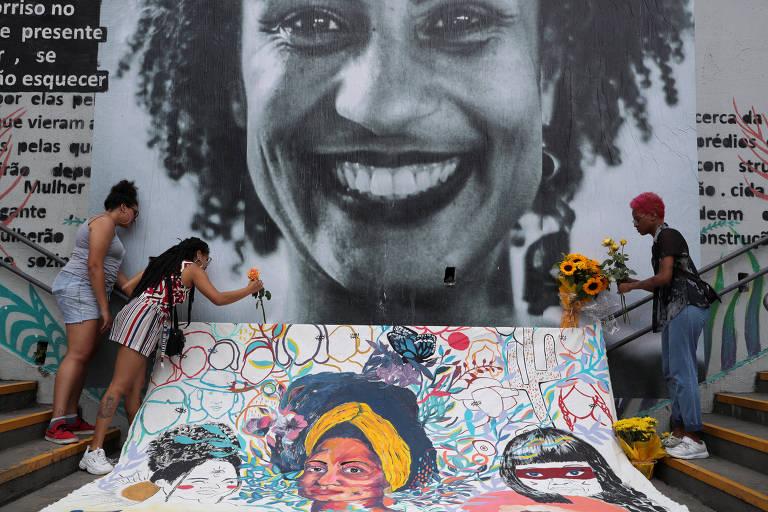 Diante de um mural com imagem de Marielle manifestantes depositam flores
