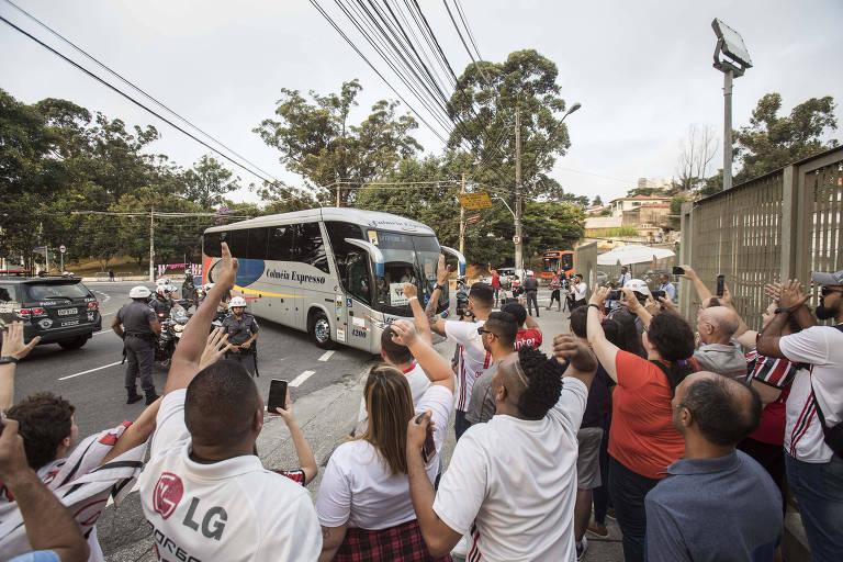 Grupo pequeno de torcedores recepciona o ônibus com a delegação são-paulina