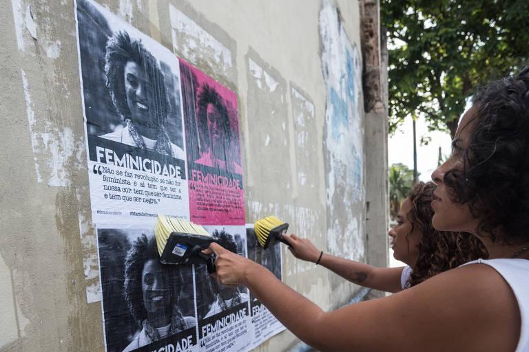Mulher cola cartaz com rosto de Marielle em muro