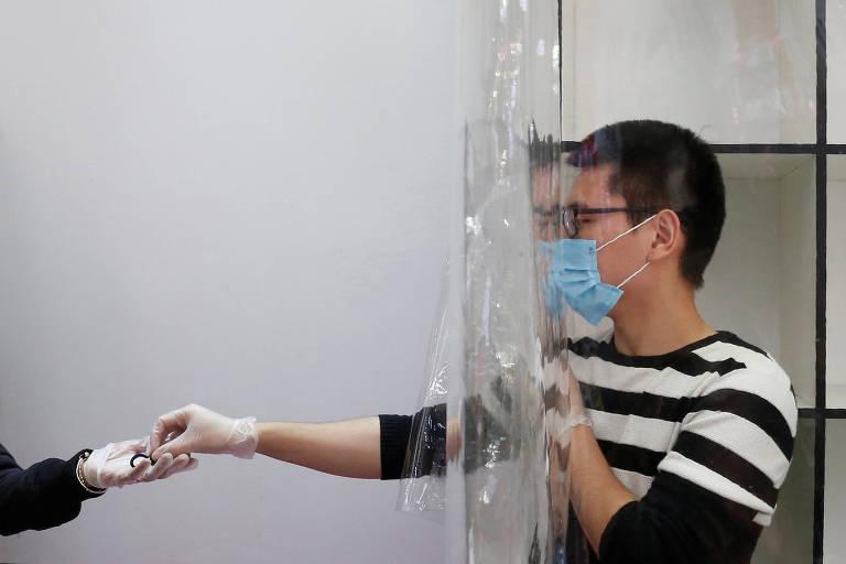 Funcionário de empresa de estoque usa máscara e se protege atrás de cortina contra o novo coronavírus em Viña del Mar, no Chile