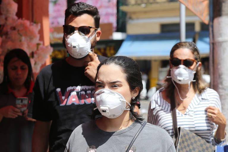 Retrato com três pessoas usando máscaras
