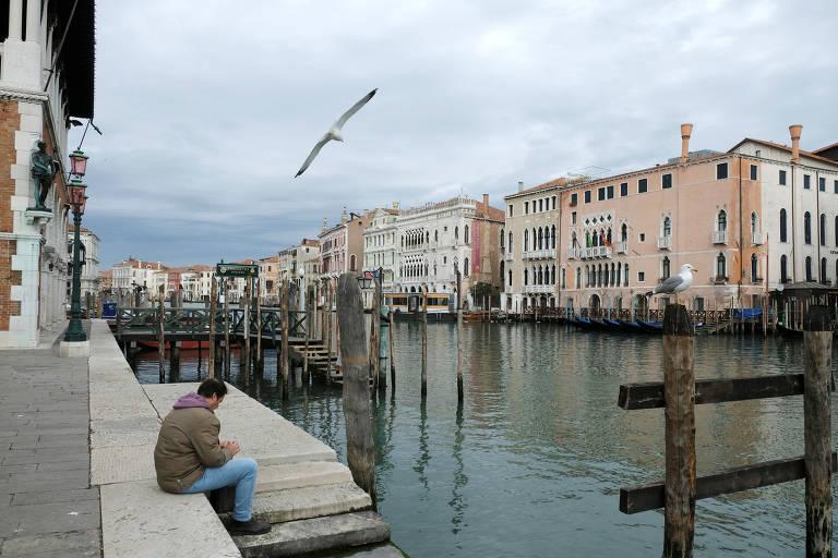 Homem solitário observa o Grand Canal, local tradicionalmente cheio de turistas em Veneza