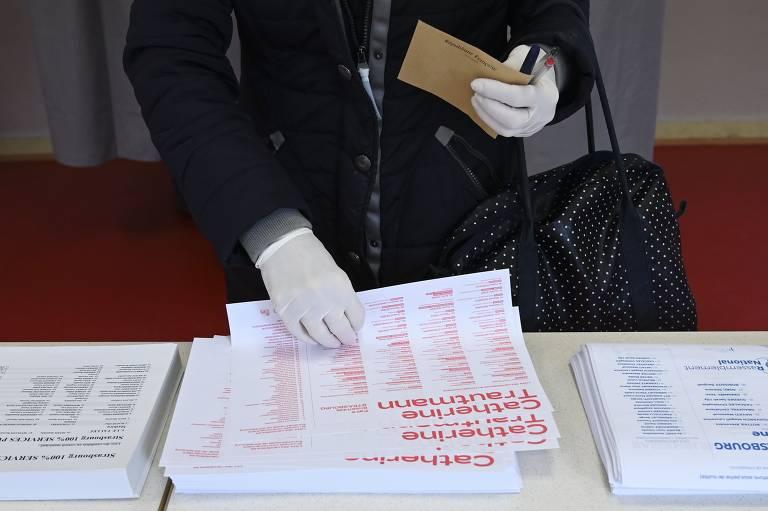 Eleitor usando luvas no primeiro turno das eleições municipais na França
