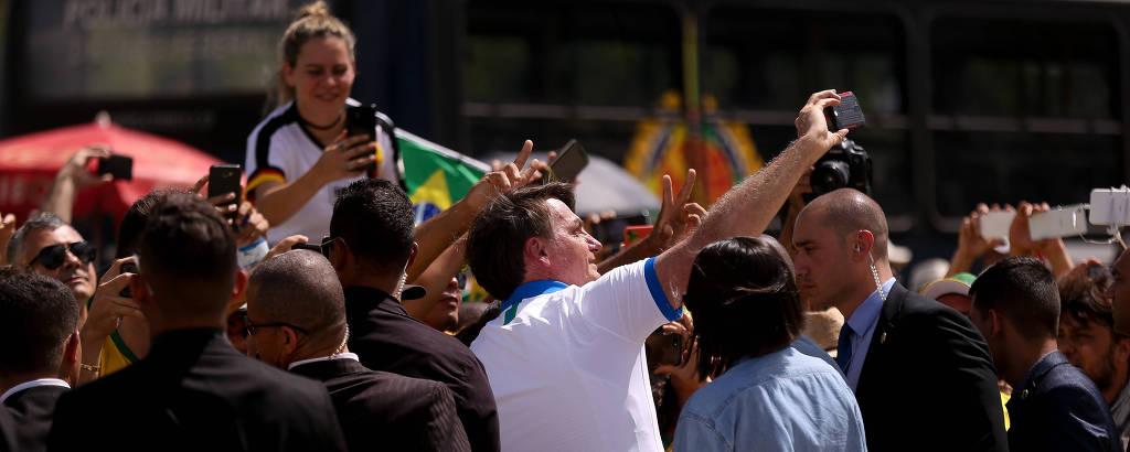 O presidente Jair Bolsonaro, de camiseta branca, segura um smartphone entre apoiadores; ao fundo, há uma menina no ombro de outra pessoa segurando uma bandeira do Brasil