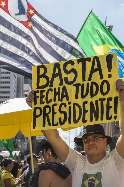 """Homem segura cartaz com """"bata! fecha tudo presidente!"""""""