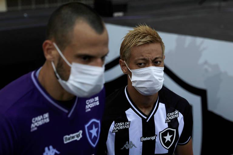 O japonês Keisuke Honda (dir.) se somou aos protestos dos jogadores do Botafogo contra a continuidade do torneio