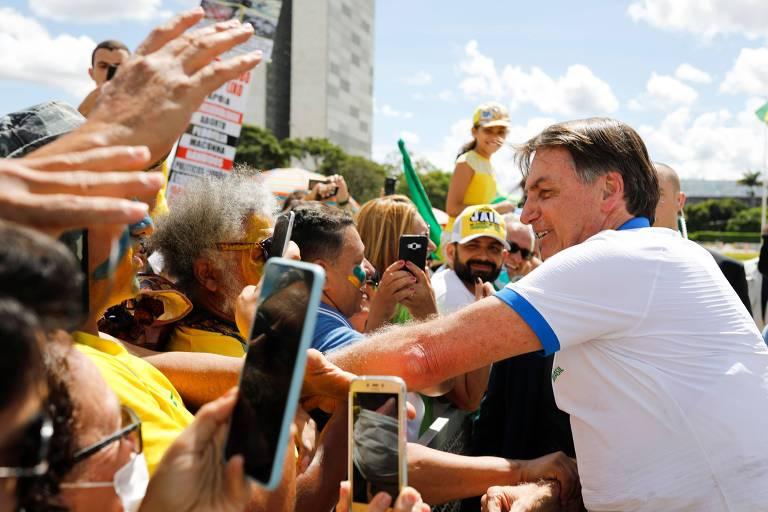 O presidente Jair Bolsonaro cumprimenta manifestantes que foram a ato pró-governo neste domingo (15), na frente do Palácio do Planalto