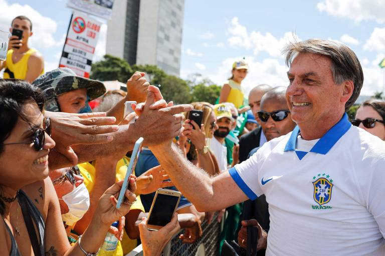 O presidente Jair Bolsonaro, com camisa branca com detalhes em azul da CBF, toca as mãos de pessoas aglomeradas para vê-lo diante do Palácio do Planalto