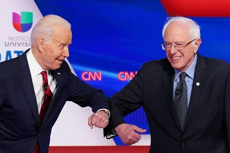 Biden (esq.) e Sanders se cumprimentam com o cotovelo