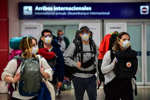 Passengers wearing face masks as a preventive measure against the spread of the COVID-19 coronavirus arrive at Ezeiza International Airport in Buenos Aires, on March 12, 2020. - The Argentine government has ordered the compulsory isolation for 14 days of people entering the South American country from the countries most affected by the new coronavirus, President Alberto Fernandez said on March 11. (Photo by Ronaldo SCHEMIDT / AFP) ORG XMIT: RSA536