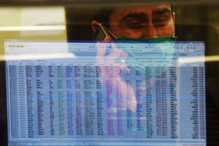 Operador do mercado financeiro trabalha de máscara no Paquistão