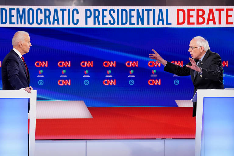 Joe Biden (esq.) e Bernie Sanders durante o debate democrata realizado domingo (15)  em Washington
