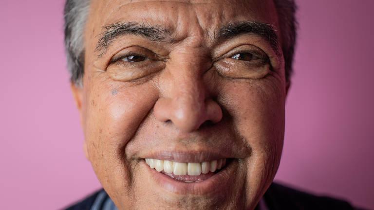 Rosto em close do ilustrador Mauricio de Sousa sorrindo; o fundo da foto é rosa