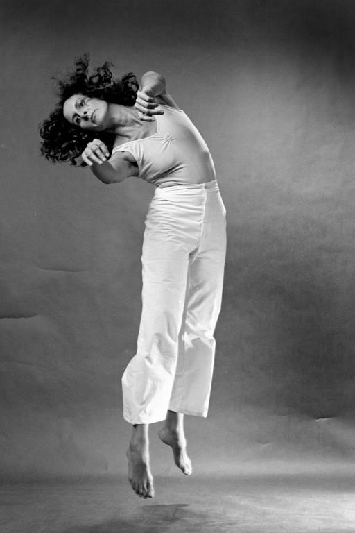 mulher de branco pula e estica os braços para frente