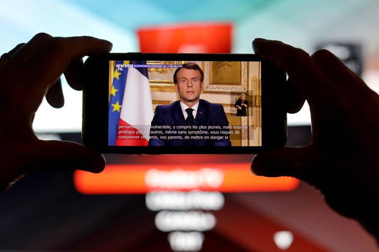 Mãos seguram um celular com a imagem do presidente da França fazendo pronunciamento