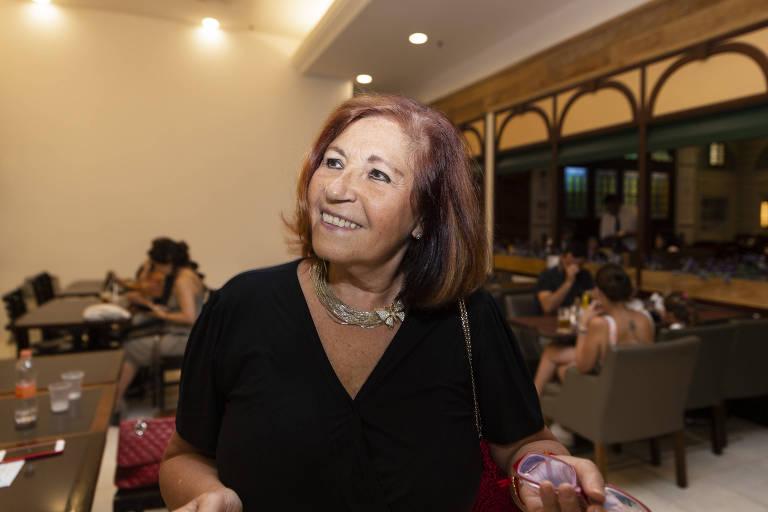 Helô Machado vestida de preto com colar prateado enfeitado com borboleta