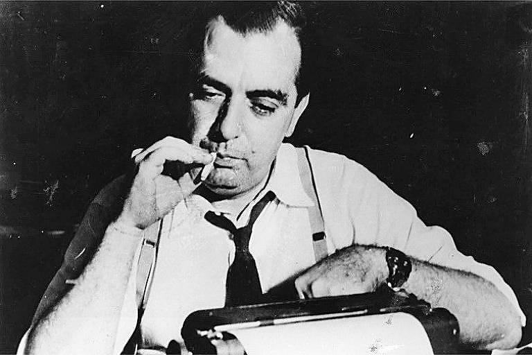 usando camisa e gravata, nelson fuma um cigarro e digita em sua máquina de escrever