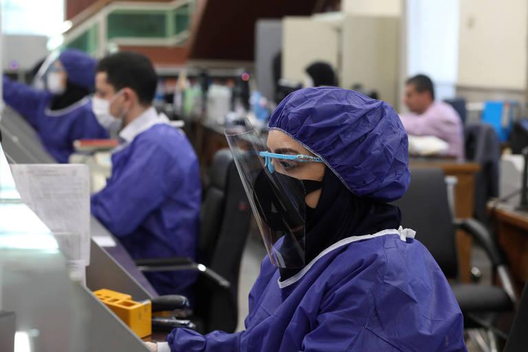 Funcionários de bancos usam máscaras e roupas de proteção em Teerã, no Irã