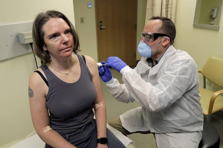 Um farmacêutico dá a Jennifer Haller, à esquerda, a primeira dose de uma potencial vacina para covid-19. Os testes estão na fase de estudo clínico para atestar a segurança da vacina