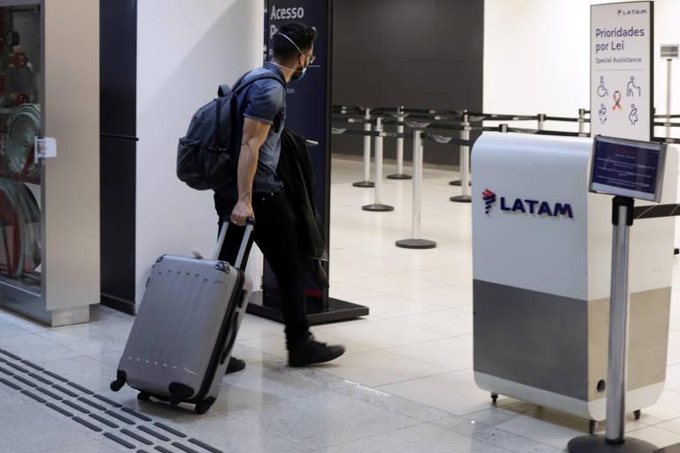 Um homem usa uma máscara de proteção enquanto caminha pelo aeroporto para fazer uma conexão em um voo doméstico da Latam