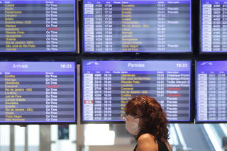 Woman wearing a face mask stands in front of arrival and departure electronic boards after the Brazilian airline Azul stated that it will cut all of its international flights out of its main hub due to the coronavirus outbreak