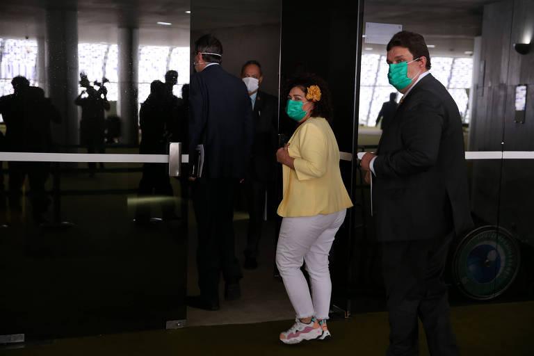 Usando máscaras, os deputados Perpétua Almeida (PC do B-AC) e Wolney Queiroz (PDT-PE) chegam ao Congresso nesta terça-feira (17)