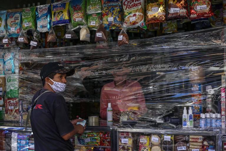 Homem com máscara compra em loja de Caracas que foi coberta por plástico para tentar conter a disseminação do coronavírus