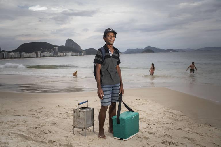 Alagoano, José Cícero Lima da Silva, 47, há 30 anos vende queijo na brasa em praias do país; nos últimos 14, no Rio; com o lucro diário, sustenta seis pessoas; na foto, ele aparece com seu fogareiro e o isopor do queijo; na praia atrás dele, há três pessoas no mar