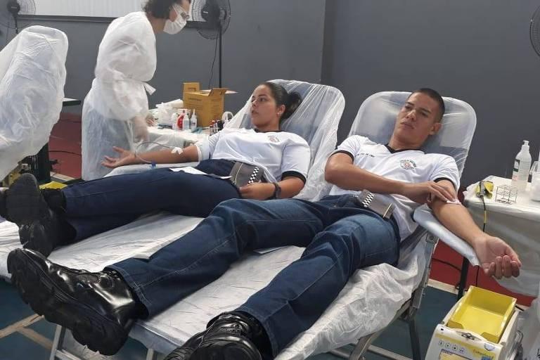 Policiais militares de SP participam de campanha de doação de sangue; na foto vemos dois PMs, uma mulher e um home, cada qual reclinado em uma maca de doação; ao fundo, uma enfermeira trabalha