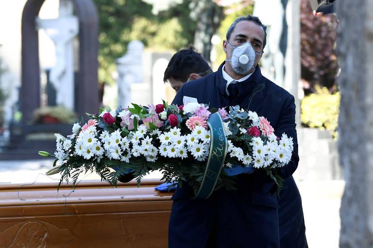 Funcionário usa máscara para transportar caixão de vítima da Covid-19 em Bérgamo, na Itália