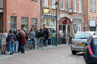 People line up to get into a coffeeshop in Amsterdam