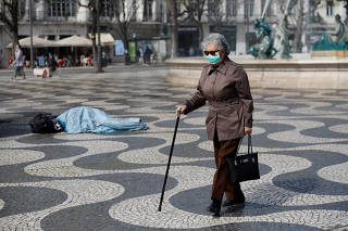 A woman is pictured wearing a mask as she walks pass a homeless person at Rossio square, in downtown Lisbon