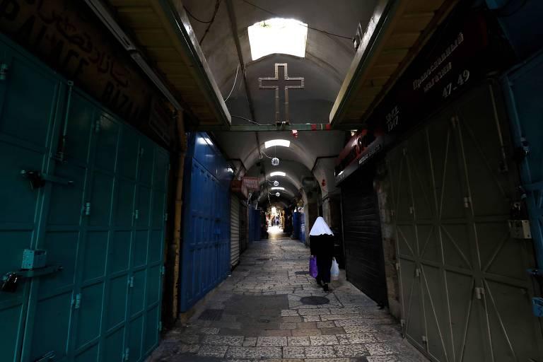 Mulher passa por lojas fechadas após medidas para combater o coronavírus em Jerusalém