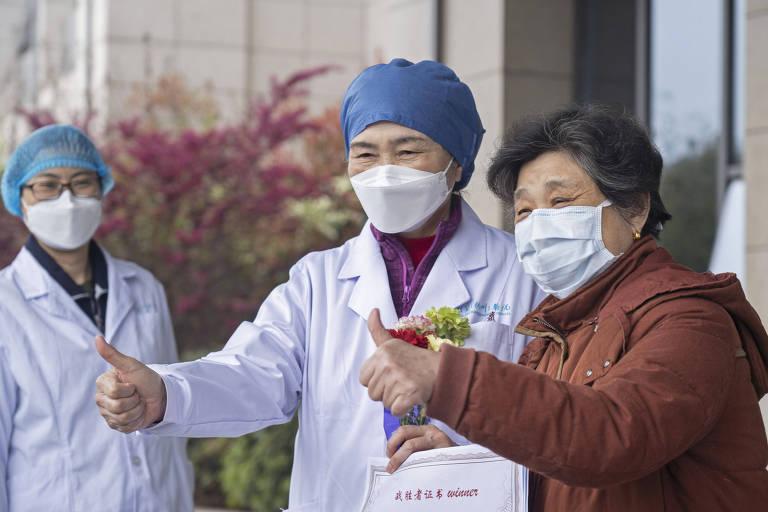 A epidemiologista chinesa Li Lanjuan posa ao lado da paciente que foi a 600ª curada de Covid-19, em hospital de Wuhan; a médica e a paciente estão de máscara, bem como a profissional de saúde que observa, ao fundo da foto, enquanto as duas fazem sinal de positivo com o polegar