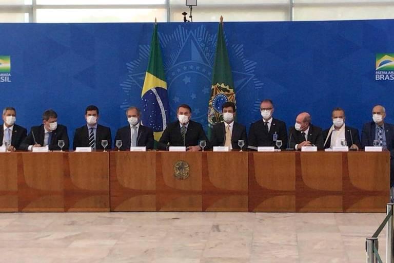O presidente Jair Bolsonaro concede entrevista usando máscara ao lado de ministros
