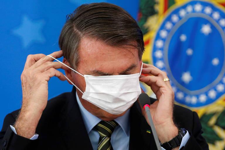 O presidente Jair Bolsonaro se atrapalha para colocar máscara cirúrgica durante entrevista coletiva e a coloca sobre os olhos
