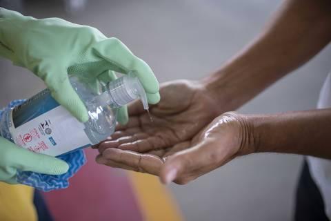 Rio de Janeiro, Rj, BRASIL. 17/03/2020;  funcionario de um supermercado aplica alcool em gel em cliente na entrada do estabelecimento  ( Foto: Ricardo Borges/Folhapress)