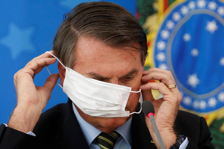O presidente Jair Bolsonaro se atrapalha para colocar máscara cirúrgica durante coletiva de imprensa, em março