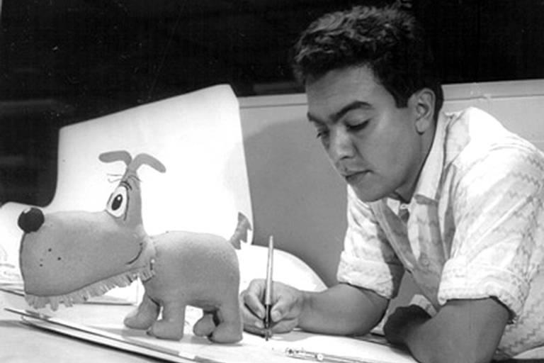 Mauricio jovem desenhando ao lado de uma estatueta do cachorrinho Bidu
