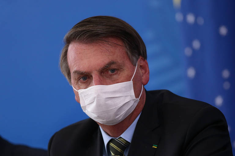 O presidente Jair Bolsonaro, de máscara, durante entrevista coletiva para falar sobre coronavírus