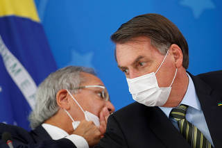 Brazil's President Jair Bolsonaro and Economy Minister Paulo Guedes, wearing protective face masks, speak during a news conference to announce measures to curb the spread of the coronavirus disease (COVID-19) in Brasilia