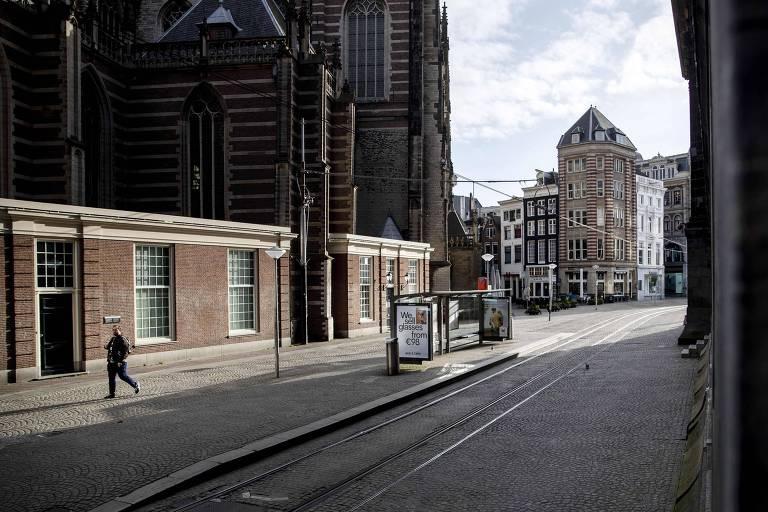 Homem caminha na praça Dam, região central de Amsterdã, esvaziada
